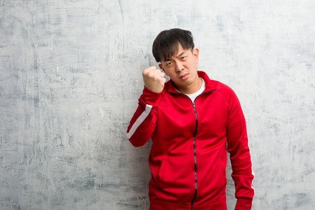 Jonge sportfitness chinees die vuist tonen aan voorzijde, boze uitdrukking