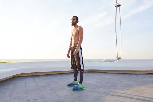 Jonge sportieve baard, rust uit na het joggen, wandelt langs de kust, luister naar favoriete liedje op koptelefoon. geniet van een geweldige ochtend!