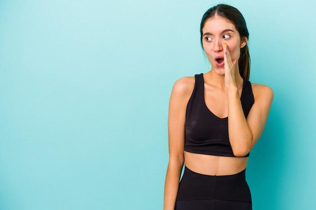 Jonge sportieve blanke vrouw geïsoleerd op blauwe achtergrond zegt een geheim heet remnieuws en kijkt opzij