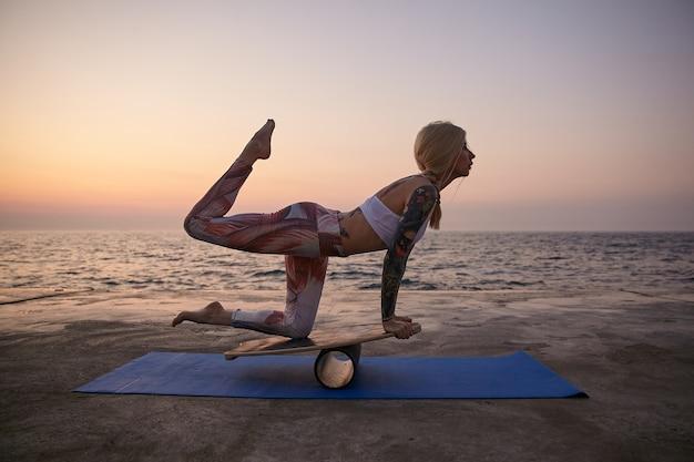 Jonge sportieve blonde dame in goede fysieke conditie poseren over zeezicht in sportieve kleding, staande op speciale sportuitrusting met opgeheven been, balanceren op een houten bord buiten op de vroege ochtend