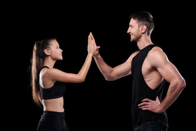 Jonge sportieve dates die naar elkaar glimlachen terwijl ze na de training een high five-gebaar maken