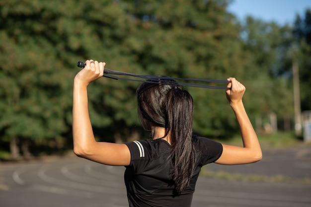 Jonge sportieve gebruinde vrouw die zich uitstrekt met een springtouw in het stadion. buitenopname met zonlicht