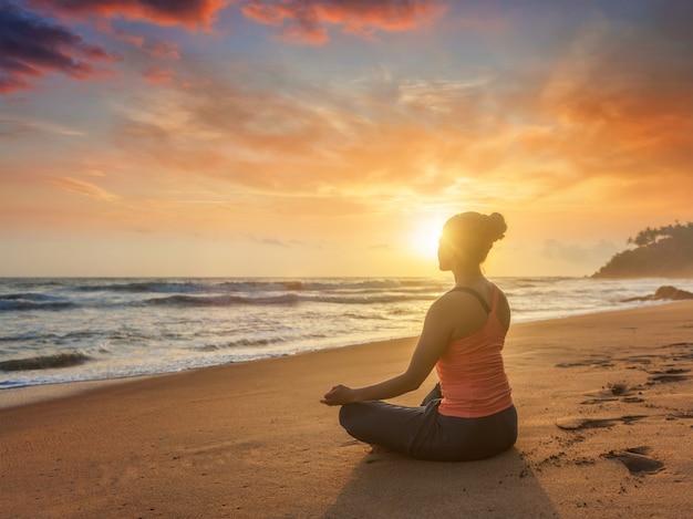 Jonge sportieve geschikte vrouw die yogaoudoors doen bij strand