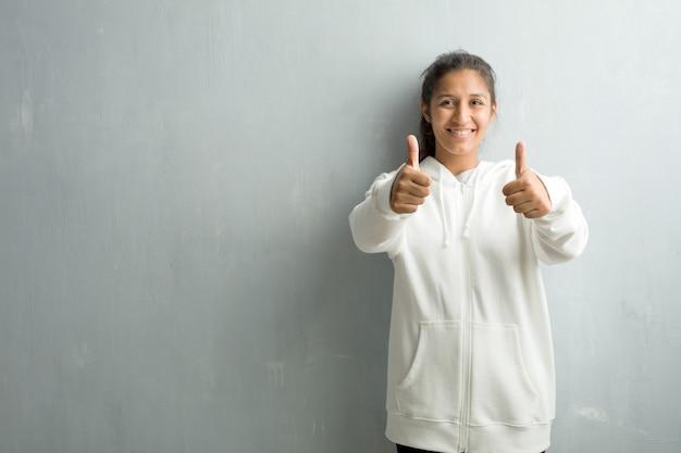 Jonge sportieve indiase vrouw tegen een sportschool muur vrolijk en opgewonden, glimlachend en het verhogen van haar