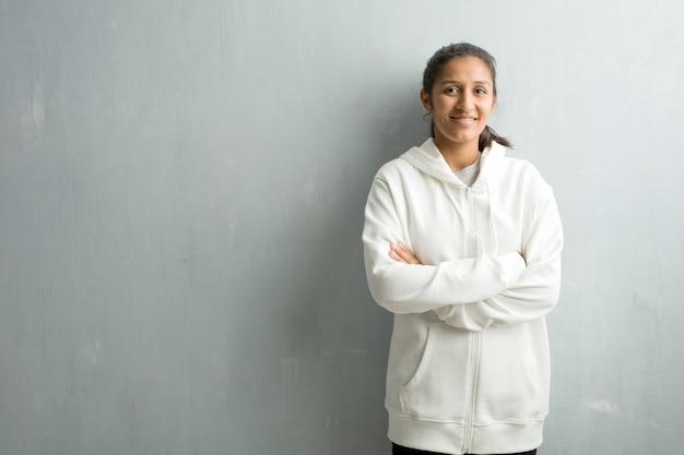 Jonge sportieve indische vrouw tegen een gymnastiekmuur die zijn wapens kruist, glimlachend en gelukkig