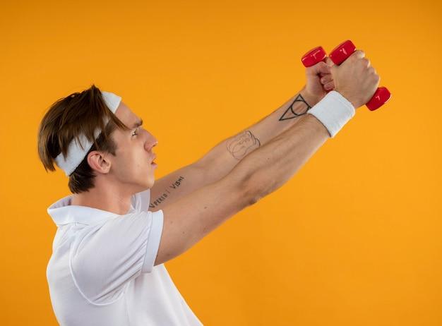 Jonge sportieve kerel die zich in profielmening bevindt die hoofdband met polsband draagt die met domoren uitoefent die op gele muur wordt geïsoleerd