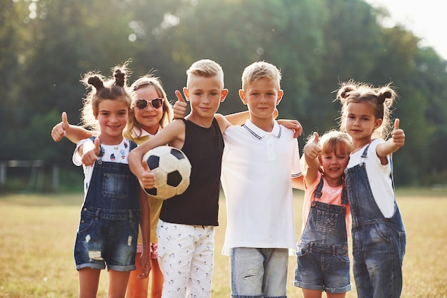 Jonge sportieve kinderen met voetbal staan samen in het veld op een zonnige dag.