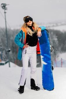 Jonge sportieve lachende vrouw in de winter met snowboard