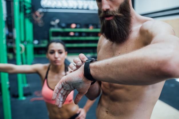Jonge sportieve man coach indoor gym met smartwatch