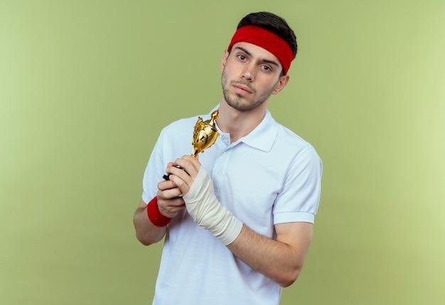 Jonge sportieve man die in hoofdband zijn trofee houdt die camera met ernstig gezicht bekijkt dat zich over groene achtergrond bevindt