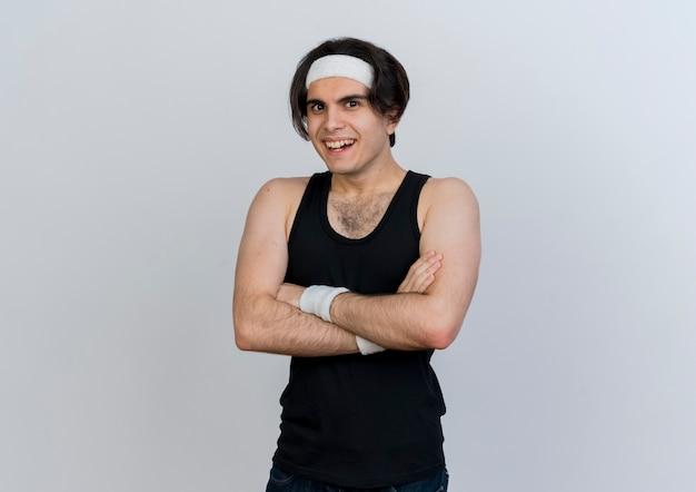 Jonge sportieve man die sportkleding en hoofdband draagt die aan de voorkant kijkt met een glimlach op het gezicht met gekruiste handen op de borst die zich over een witte muur bevindt
