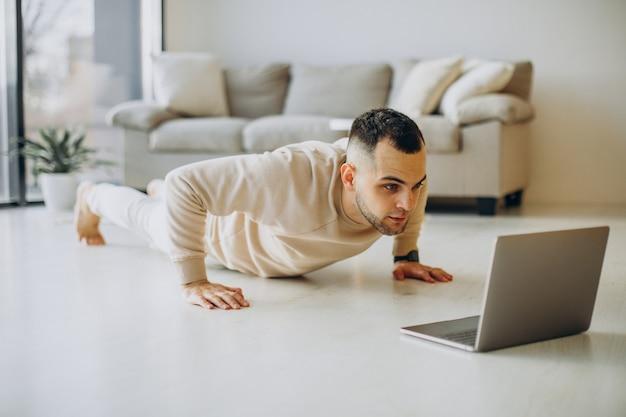 Jonge sportieve man die thuis yoga beoefent Gratis Foto