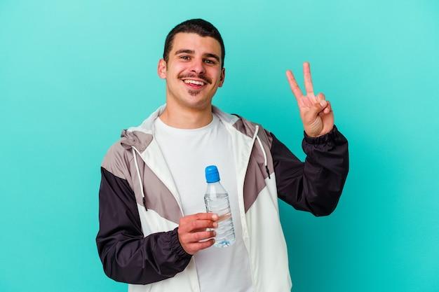 Jonge sportieve man drinkwater geïsoleerd op blauwe muur vrolijk en zorgeloos met een vredessymbool met vingers