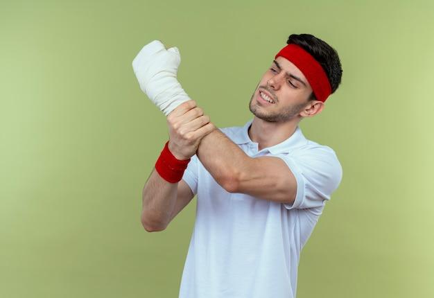 Jonge sportieve man in hoofdband die zijn verbonden hand raakt die pijn voelt die zich over groene achtergrond bevindt