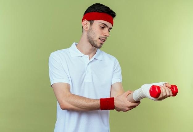 Jonge sportieve man in hoofdband die zijn verbonden pols raakt die pijn over groen voelen