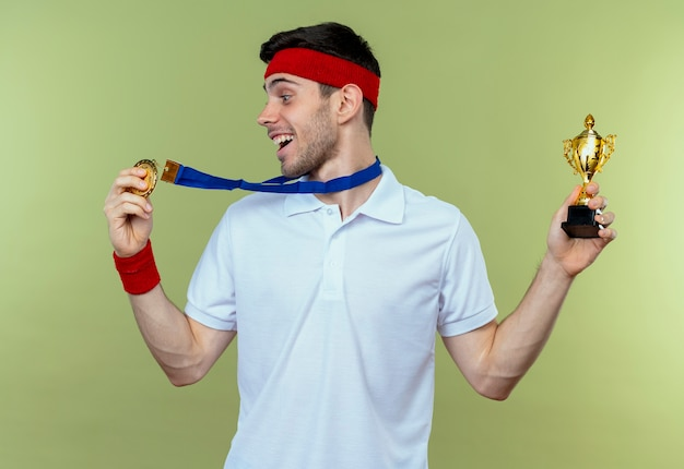 Jonge sportieve man in hoofdband met gouden medaille om de nek die zijn trofee blij en opgewonden over groen houdt