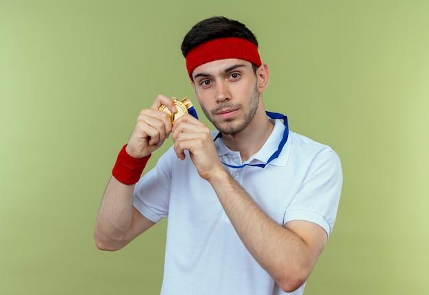 Jonge sportieve man in hoofdband met gouden medaille om nek die zijn medaille toont die er zelfverzekerd uitziet over groen