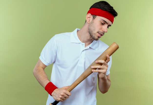 Jonge sportieve man in hoofdband met honkbalknuppel kijken naar het staande over groene achtergrond