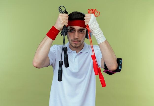 Jonge sportieve man in hoofdband met hoofdtelefoons en smartphone-armband met twee springtouwen over groen