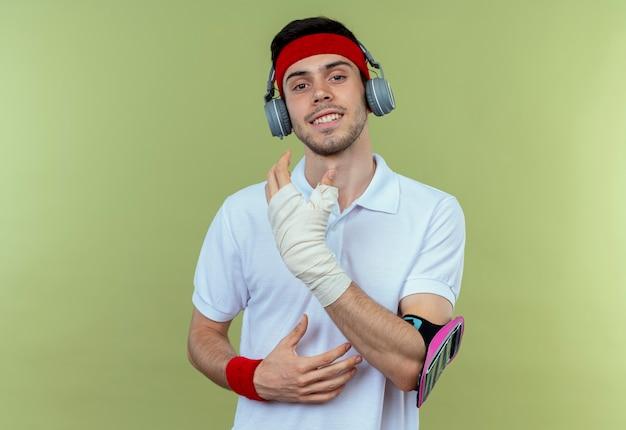 Jonge sportieve man in hoofdband met koptelefoon en smartphone armband kijken camera lachend met blij gezicht staande over groene achtergrond