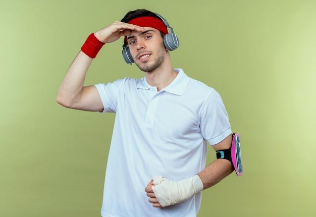 Jonge sportieve man in hoofdband met koptelefoon en smartphone armband ver weg kijken met hand boven het hoofd staande over groene achtergrond