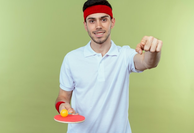 Jonge sportieve man in hoofdband met racket en bal voor tafeltennis kijken camera glimlachend wijzend met wijsvinger naar je staande over groene achtergrond