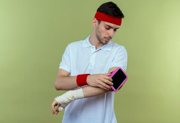 Jonge sportieve man in hoofdband met smartphone armband kijken met ernstig gezicht over groen
