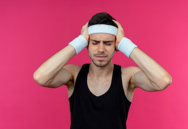 Jonge sportieve man in hoofdband op zoek onwel met zijn hoofd met handen die lijden aan sterke hoofdpijn staande over roze achtergrond