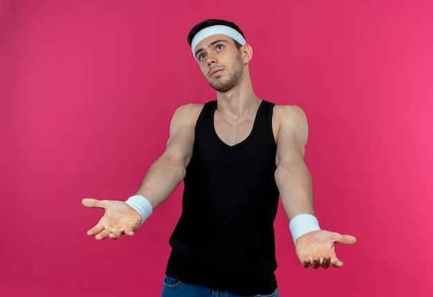Jonge sportieve man in hoofdband op zoek verward en onzeker schouders ophalen over roze