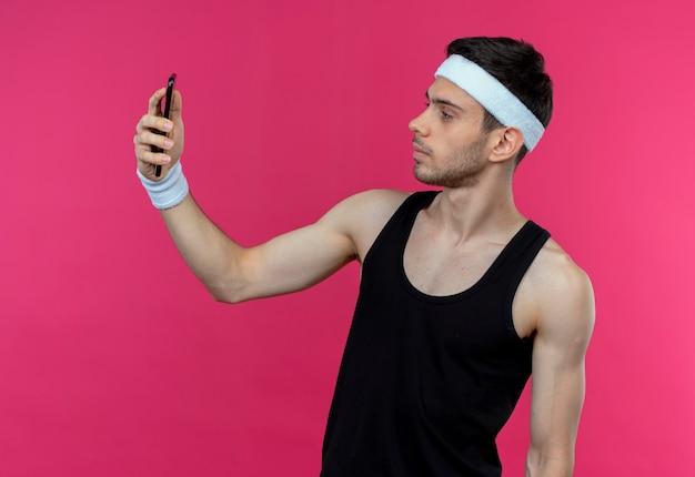 Jonge sportieve man in hoofdband selfie met zijn smartphone over roze