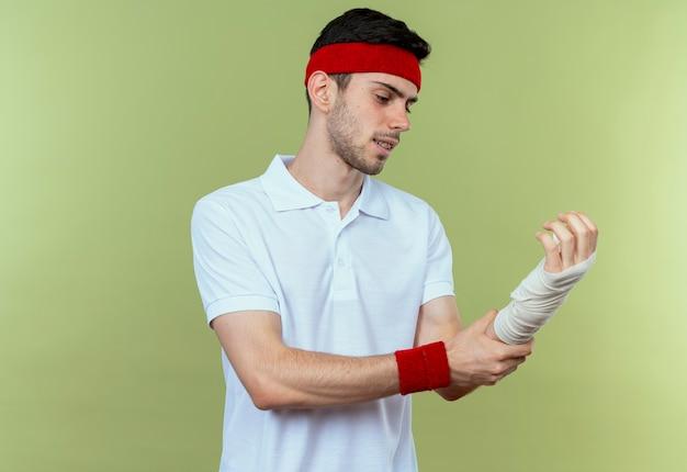 Jonge sportieve man in hoofdband wat betreft zijn verbonden pols die pijn voelt die zich over groene achtergrond bevindt