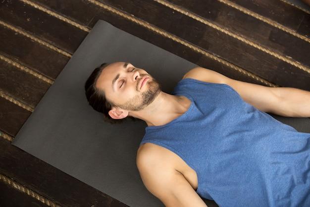 Jonge sportieve man liggend in lichaamsbeweging
