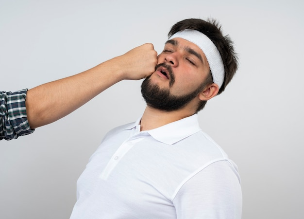 Jonge sportieve man met gesloten hoofdband en polsband geslagen door iemand geïsoleerd op een witte muur