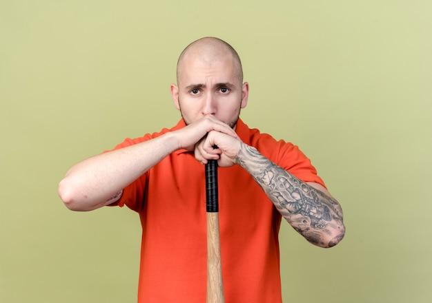 Jonge sportieve man met honkbalknuppel onder de kin