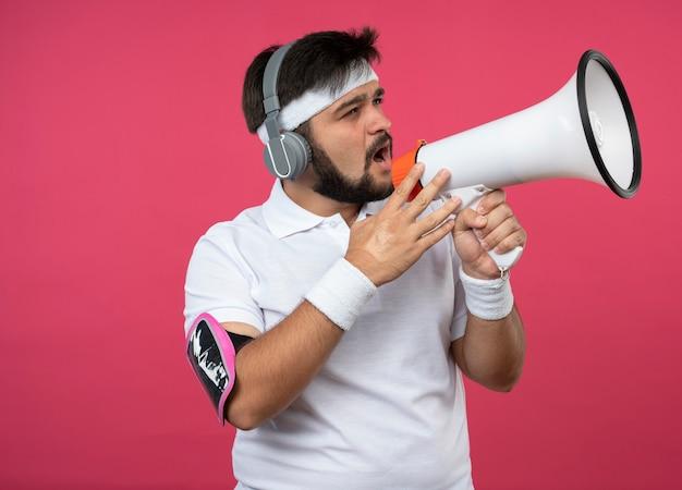 Jonge sportieve man met hoofdband en polsbandje met koptelefoon en telefoonarmband spreekt op luidspreker