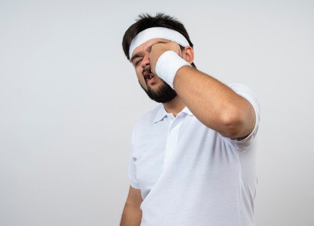 Jonge sportieve man met hoofdband en polsbandje slaan zichzelf geïsoleerd op wit met kopie ruimte