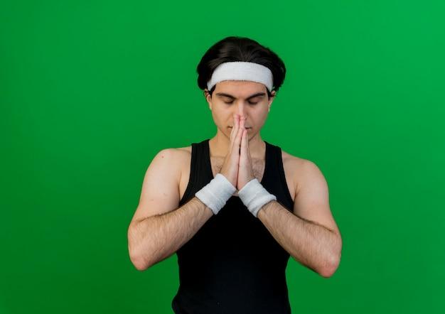 Jonge sportieve man met sportkleding en hoofdband hand in hand samen als bidden