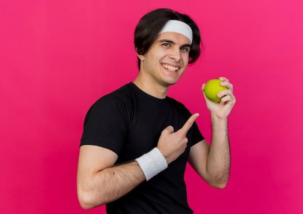 Jonge sportieve man met sportkleding en hoofdband met groene appel wijzend met wijsvinger naar het