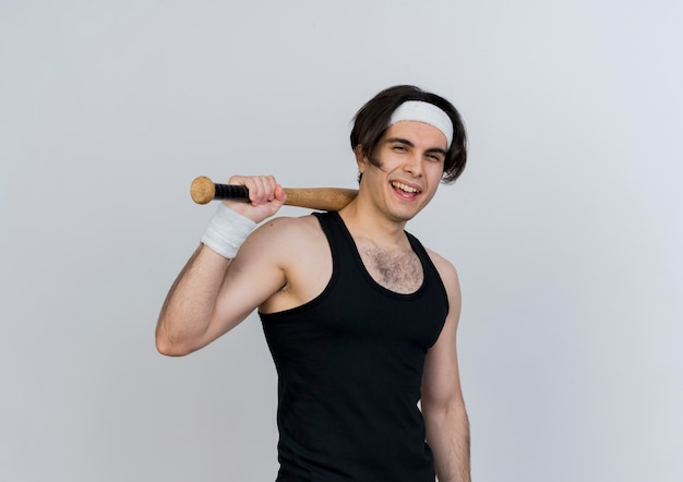 Jonge sportieve man met sportkleding en hoofdband met honkbalknuppel kijken voorkant glimlachend en knipogen staande over witte muur
