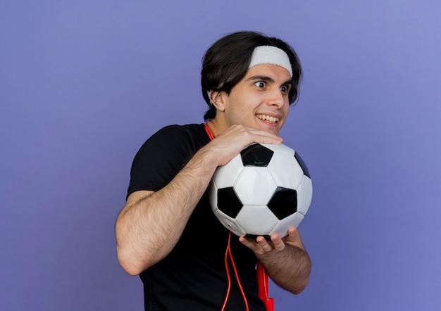Jonge sportieve man met sportkleding en hoofdband met springtouw om nek met voetbal opzij glimlachend sluw