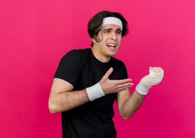 Jonge sportieve man met sportkleding en hoofdband wijzend met arm naar zijn verbonden pols pijn voelen