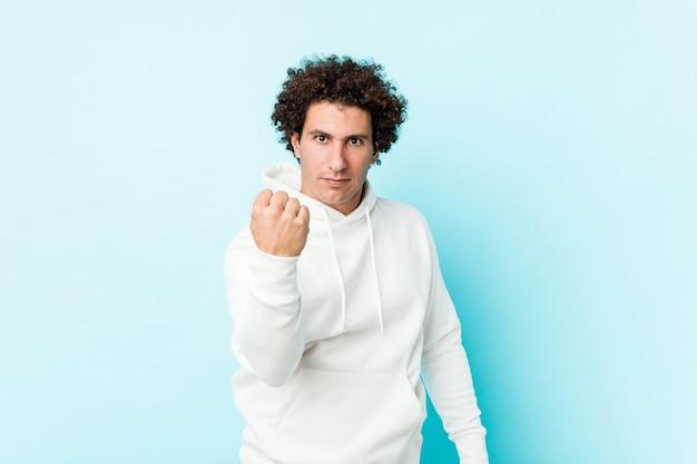 Jonge sportieve man tegen een blauwe muur met vuist met agressieve gelaatsuitdrukking.