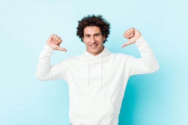 Jonge sportieve man tegen een blauwe muur voelt zich trots en zelfverzekerd, een voorbeeld om te volgen.