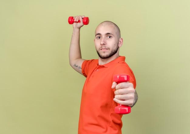 Jonge sportieve man trainen met halters geïsoleerd op olijfgroene muur