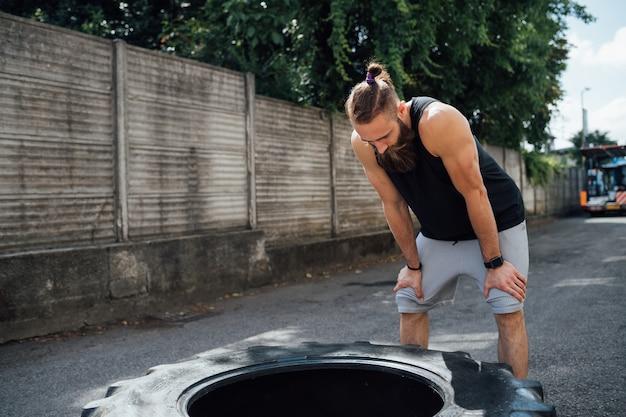 Jonge sportieve man uitgeput herstellende outdoor gym een pauze te nemen