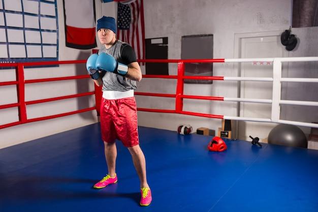 Jonge sportieve mannelijke bokser in bokshandschoenen bereidt zich voor op de strijd in de reguliere boksring