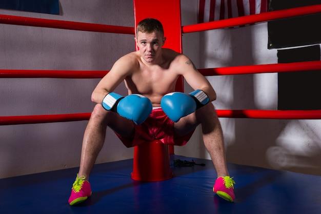 Jonge sportieve mannelijke bokser met blote borst in bokshandschoenen die dichtbij rode hoek zitten