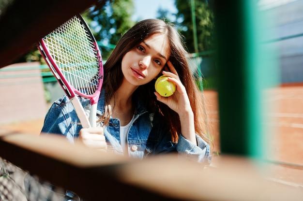 Jonge sportieve meisjesspeler met tennisracket op tennisbaan.