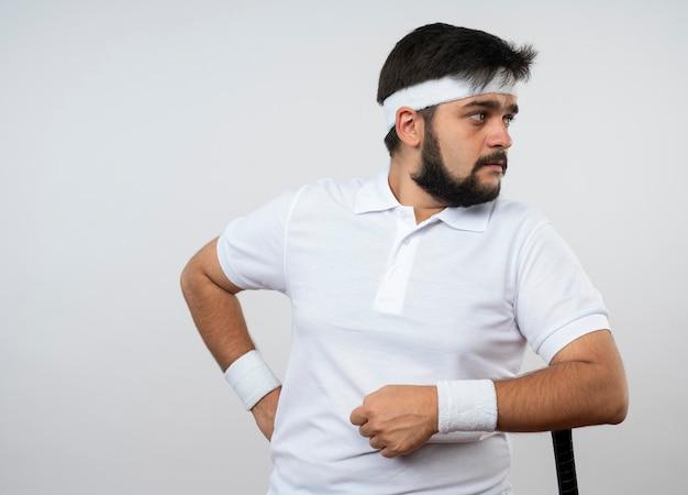 Jonge sportieve mens die kant bekijkt die hoofdband en polsband draagt die elleboog op honkbalknuppel zet die op witte muur met exemplaarruimte wordt geïsoleerd