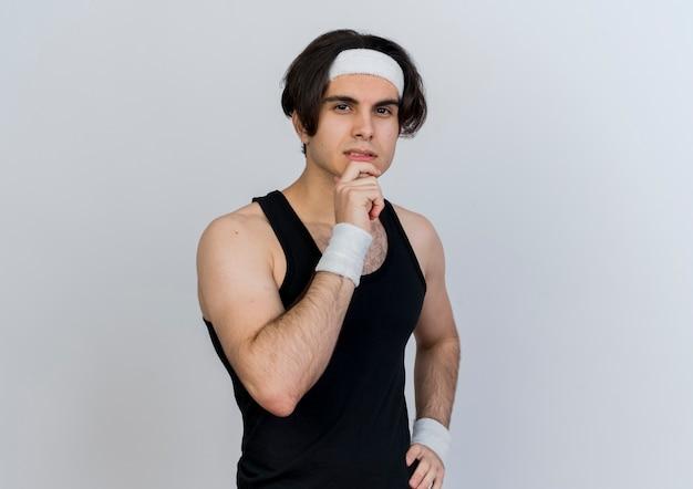 Jonge sportieve mens die sportkleding en hoofdband draagt die voorzijde met hand op kin bekijkt die zich over witte muur bevindt
